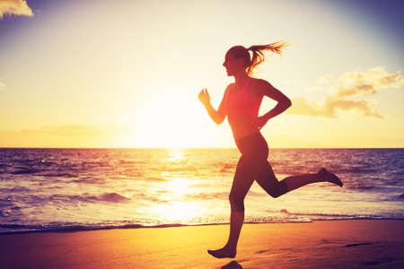 sunrise lake: Woman running on the beach at sunset Stock Photo