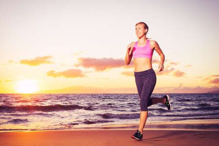 Athletic fitness woman running on the beach at sunset photo