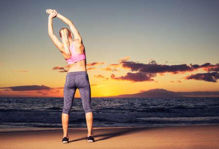 Atletische fitness vrouw die zich uitstrekt op het strand bij zonsondergang