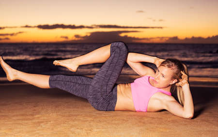 sit: Fitness young woman doing sit ups on beach at sunset. Outdoor workout.