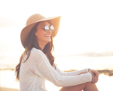 Stijlvolle Fashion Vrouw op het strand bij zonsondergang, heldere, warme zonnige Portret