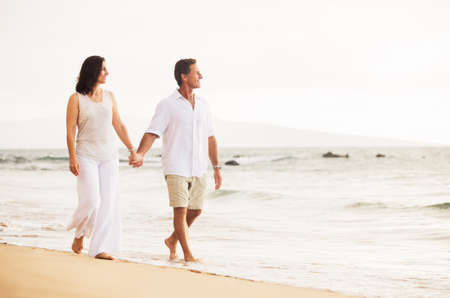 Mature Retired Couple Enjoying Sunset Walk on the Beach photo