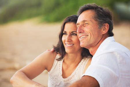 幸せなロマンチックな成熟したカップルは、ビーチで夕日を楽しむ