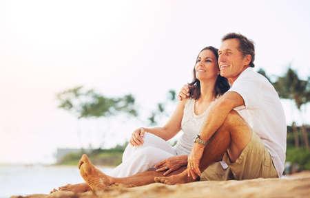 ビーチで夕日を楽しむ幸せなロマンチックな成熟したカップル
