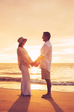 Romantic Mature Couple Enjoying at Sunset on the Beach in Hawaii photo