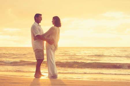 Romantic Retired Couple Relaxing on Beach Vacation at Sunset photo