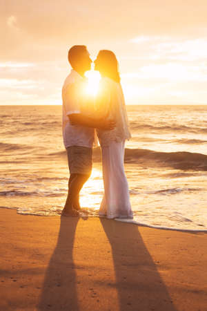 Romantic Mature Couple Kissing at Sunset on the Beach photo