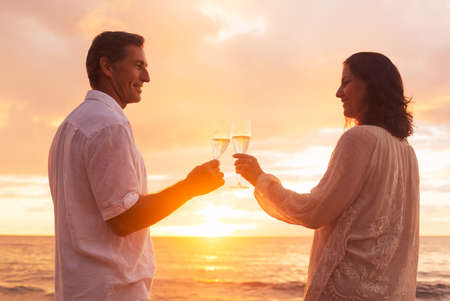 retirement couple: Happy Romantic Couple Enjoying Glass of Champagne at Sunset on the Beach. Vacation Travel Retirement Anniversary Celebration.