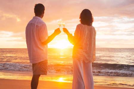 anniversaire: Romantic Couple heureux en appréciant un verre de champagne au coucher du soleil sur la plage. Vacances Celebration Voyage Retirement anniversaire.