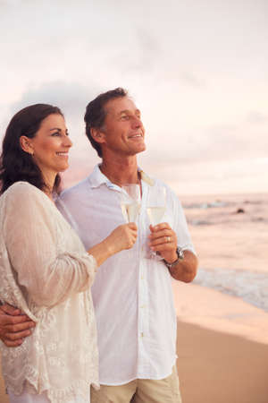 Happy Romantic Mature Couple Drinking Champagne on the Beach at Sunset.  photo