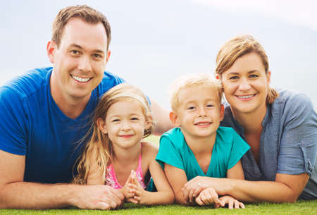 Portrait of Happy Family Outside on Grass photo