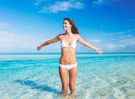 Mooie vrouw in bikini op tropisch wit zandstrand Stockfoto