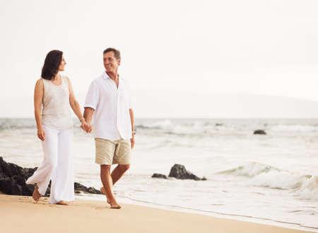 Mature Retired Couple Enjoying Sunset Walk on the Beach