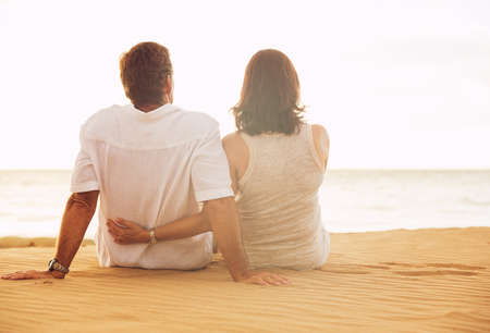 Mature Retired Couple Enjoying Sunset on Beach Vacation photo