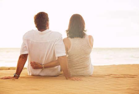 Mature Teruggetrokken Paar genieten van zonsondergang op het strand vakantie Stockfoto