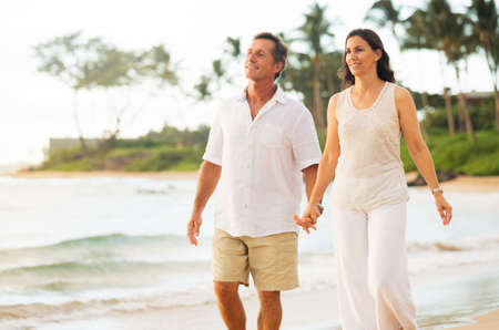 ロマンチックな成熟したカップルはビーチで散歩を楽しんで