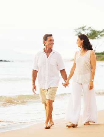Mature Retired Couple Enjoying Sunset Walk on the Beach photo