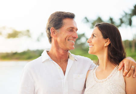 Mature Retired Couple Enjoying Tropical Sunset Beach Vacation Stock Photo