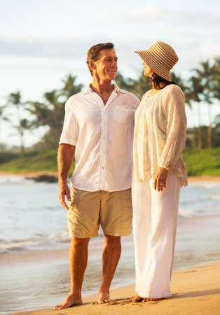 Mature Retired Couple Enjoying Sunset on Beach Vacation photo
