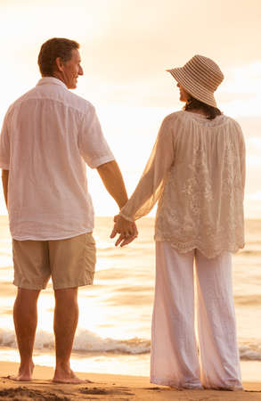 Romantic Mature Couple Holding Hands Enjoying at Sunset on the Beach photo