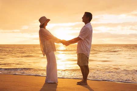 Romantic Mature Couple Enjoying at Sunset on the Beach in Hawaii