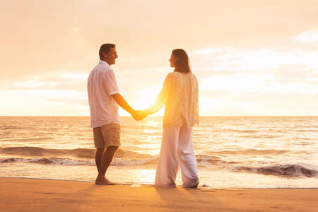 Romantic Senior Couple Enjoying Sunset at the Beach photo