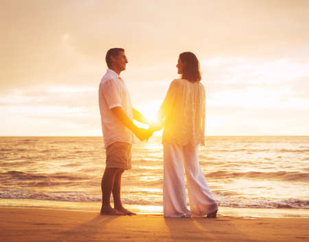 Romantic Mature Couple Enjoying Sunset at the Beach photo