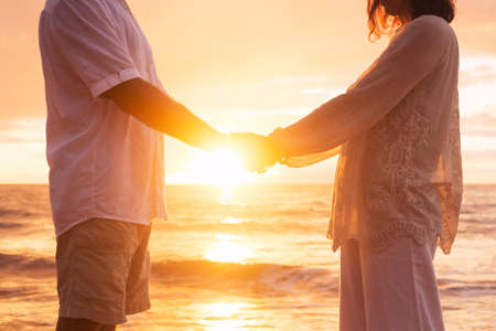 Romantic Mature Senior Couple Holding Hands Enjoying at Sunset on the Beach