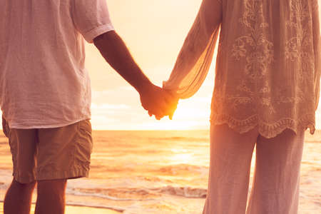 Romantic Mature Senior Couple Holding Hands Enjoying at Sunset on the Beach photo