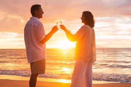 anniversary beach: Happy Romantic Mature Couple Enjoying Glass of Champagne at Sunset on the Beach