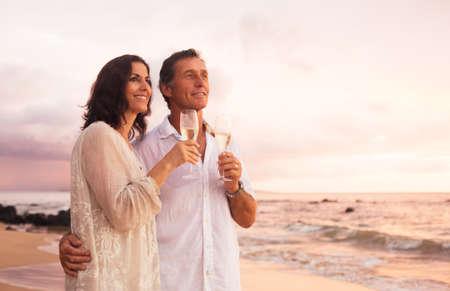 행복 한 로맨틱 성숙한 커플 마시는 샴페인 해변에서 석양. 휴가 여행 퇴직 기념일 축하. 스톡 콘텐츠