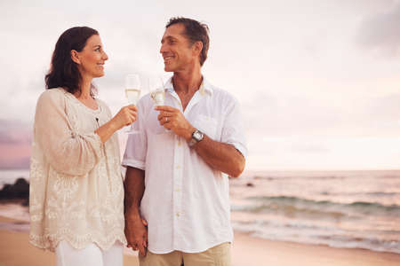 anniversary beach: Happy Romantic Mature Couple Drinking Champagne on the Beach at Sunset. Vacation Travel Retirement Anniversary Celebration.