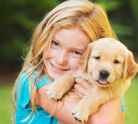 puppy love: Adorable Linda Chica joven con el perrito del golden retriever Foto de archivo
