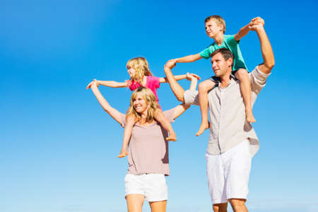 Happy Healthy Family of Four having Fun on Tropical Beach photo