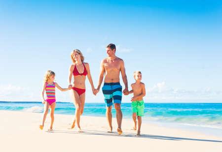 beach resort: Familia de cuatro miembros feliz que se divierten caminando por la playa Foto de archivo