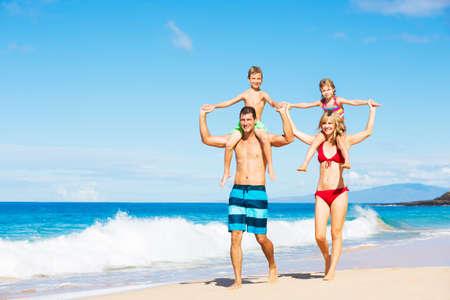child bikini: Happy Family Having Fun on the Beach Stock Photo