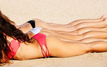 Beautiful Girls in Sexy Bikinis Sunbathing on the Beach. Summer fun lifestyle. photo