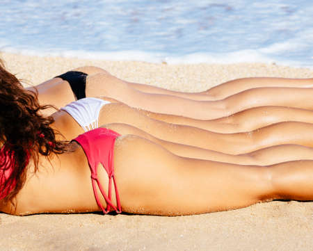 thong woman: Beautiful Girls in Bikinis Sunbathing on the Beach. Summer fun lifestyle.