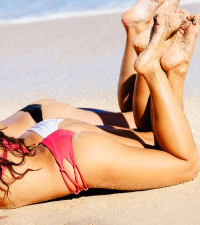 Beautiful Girls in Small Sexy Bikinis Sunbathing on the Beach. Summer fun lifestyle. Stock Photo