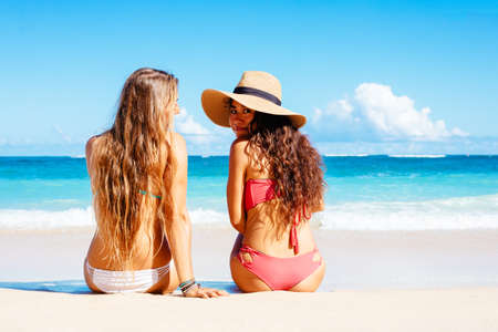 Two Attractive Girls in Bikinis Sitting on Sunny Tropical Beach photo