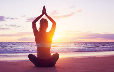 Young healthy woman practicing yoga on the beach at sunset Standard-Bild