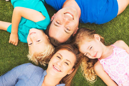 family day: Portrait of Happy Family of Four Outside On the Grass Stock Photo