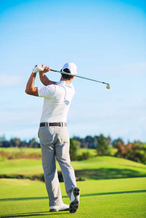 Man Playing Golf on Beautiful Sunny Green Golf Course Hitting Golf Ball down the Fairway.