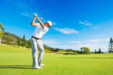 golfing: Golfer Hitting Golf Shot met Club op de Cursus Stockfoto