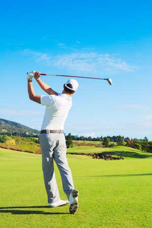 golfing: Man Playing Golf on Beautiful Sunny Green Golf Course Hitting Golf Ball down the Fairway.