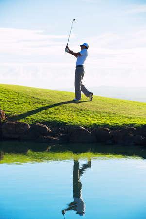 美しいコースでは、反射水でゴルフの男のシルエット 写真素材