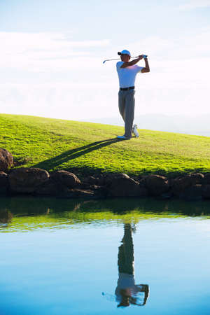 Silhouette of Man Playing Golf on Beautiful Course, Reflection in Water photo