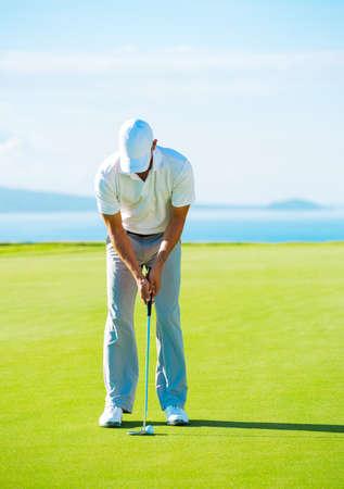 골퍼가 퍼팅에 녹색 구멍에 골프 공을 치는 스톡 콘텐츠