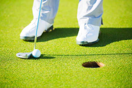 Man Putting Golf Ball into the Hole, Close up detail Shot photo