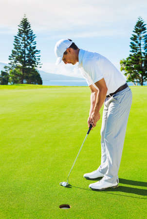 putter: Golfer on Putting Green Hitting Golf Ball into the Hole
